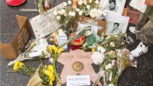 Des anonymes déposent des fleurs et des souvenirs devant l'étoile d'Aretha Franklin sur le Hollywood Walk of Fame, le 16 août 2018 à Los Angeles.