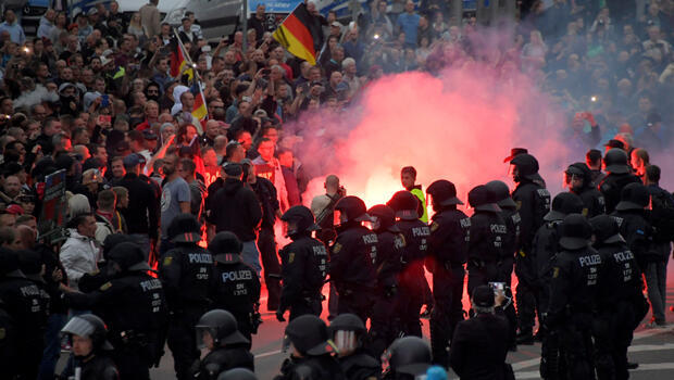 Policías antidisturbios montan guardia mientras los partidarios de la derecha protestan después de que un hombre alemán fuera apuñalado el pasado fin de semana en Chemnitz , Alemania, el 27 de agosto de 2018.