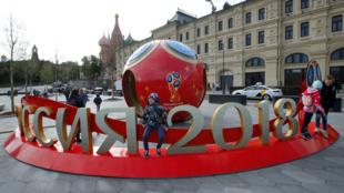 La gente se reúne cerca de las decoraciones de la próxima Copa Mundial de la FIFA 2018, cerca a la Catedral de San Basilio vista de fondo, en el centro de Moscú, Rusia, el 7 de junio de 2018.