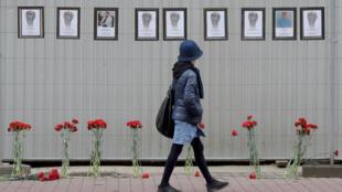 امرأة تسير أمام صور للعاملين الطبيين الروس الذين توفوا  بسبب كوفيد-19 خارج مستشفى في سانت بطرسبرغ. وقد توفي أكثر من 70 منهم حتى الآن.