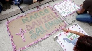 Los manifestantes se sientan junto a un cartel con los nombres de los tres estudiantes de cine secuestrados y asesinados por hombres armados después de haber sido confundidos con miembros de una pandilla rival en el estado de Jalisco, durante una protesta en Ciudad de México, México.