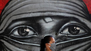 A woman wearing a protective mask walks in front of a graffiti amid the coronavirus disease outbreak in Rio de Janeiro, Brazil, May 13, 2020.