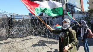 Des manifestants brandissent le drapeau palestinien près de l'ambassade américaine à Awkar, au nord de Beyrouth, le 2 février 2020.