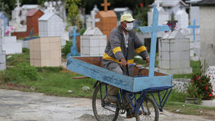 Ulisses Xavier, 52, who has worked for 16 years at Nossa Senhora cemetery in Manaus, Brazil, rides a bike carrying a cross during his shift on May 7, 2020. The cemetery has seen a surge in the number of new graves after the outbreak of Covid-19.