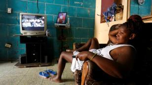 Una mujer descansa en un sofá mientras el televisor muestra la transmisión de una sesión de la Asamblea Nacional en la que se debatía sobre el proyecto de nueva Constitución. La Habana, Cuba, el 21 de julio de 2018.