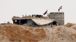 Banderas nacionales rusas y sirias ondean cerca de la aldea de Zor Magar, en el norte de Siria y cerca de la frontera con Turquía, el 23 de octubre.