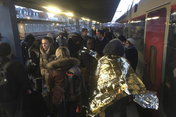 Passengers are seen on the platform at Arras, in northeastern France on January 13, 2017 as they are transferred from one train to another after a Brussels-Paris bound train hit technical difficulties in bad weather.