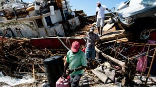 Des rescapés retrouvent des objets dans un bateau après le passage de l'ouragan Dorian, le 5 septembre 2019 dans l'île d'Abaco, dans les Bahamas.