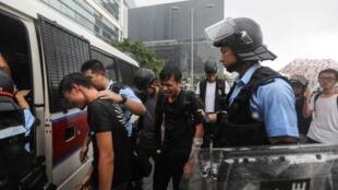 Des jeunes manifestants arrêtés, lundi 1er juillet au matin, à Hong Kong.