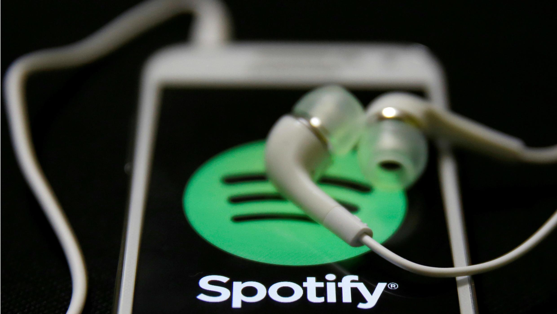 FOTO DE ARCHIVO: Los auriculares se ven en la parte superior de un smartphone con el logotipo de Spotify el 20 de febrero de 2014.