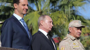 Syrian President Bashar al-Assad's (L, pictured December 2017 with Russian President Vladimir Putin, C) regime, supported by Moscow, in December 2019 relaunched its offensive against the northwestern region