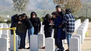 Members of the Gutierrez family mourn graveside, during a non customary military burial service amid an outbreak of the coronavirus disease (COVID-19), for Robert Gutierrez, who was given a Purple Heart award for serving in the Vietnam War and passed away of a non-coronavirus related death, at the Bakersfield National Cemetery in Arvin, California, U.S., April 3, 2020. The family was given limited social distance to the casket, only ten members allowed to attend the funeral and a ceremonial U.S. flag wasn't given due to precautions from the coronavirus.